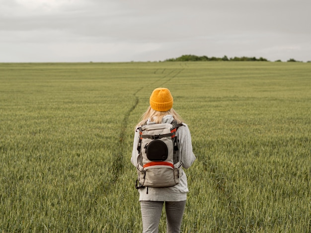 Female with backpack in green field