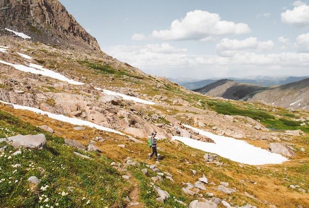 Femmina con uno zaino che fa un'escursione giù una montagna sotto un cielo nuvoloso al giorno