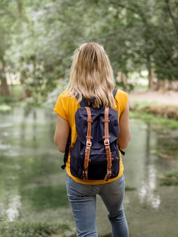 Female with backpack at lake