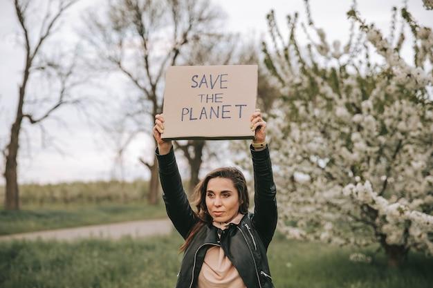 Женщина с баннерами протестует против глобального потепления ради спасения планеты земля