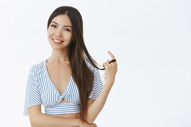 Женщина в короткой полосатой блузке играет с прядью волос и радостно улыбается, флиртует во время разговора