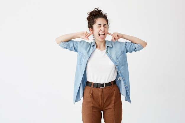 Female with dark hair in bun, wears denim shirt and brown trousers, plugs ears with fingers, makes grimace. girl can t stand loud sound, frowns face, poses with closed eyes and sticks out tongue