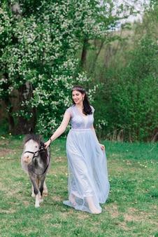 美しいドレスを着た黒髪の女性は灰色のポニーと森の中を歩きます
