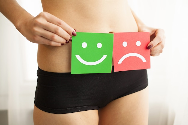 Female with fit slim body in panties holding two card with sad smiley and happy face near her stomach.