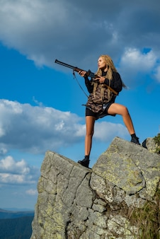 Female with a gun woman hunter with a gun calibers of hunting rifles hunter with a shotgun in a trad...