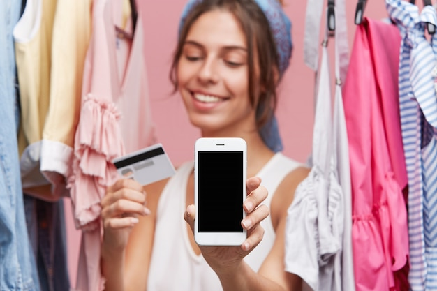 Female with happy expression standing near rack with clothes, keeping in hands credit card and modern mobile phone, being glad to buy garment online. people, online shopping