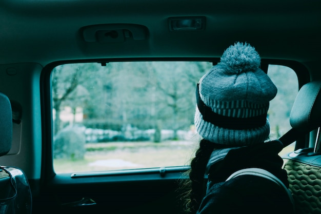 Female with a hat sitting inside a car looking out the window
