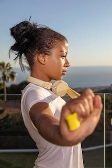 自宅でフィットネスをしているヘッドフォンを持つ女性