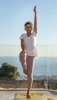 Femmina con le cuffie facendo fitness a casa