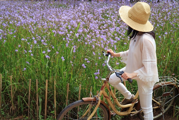 Female with her bicycle enjoy beautiful pastel purple flower field