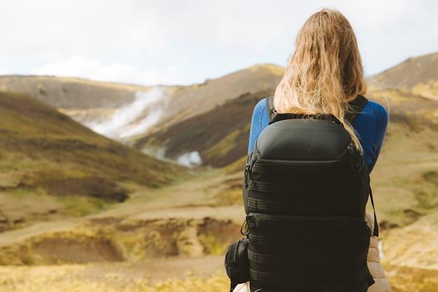 アイスランドの美しい山々を見ているハイキングバックパックを持つ女性