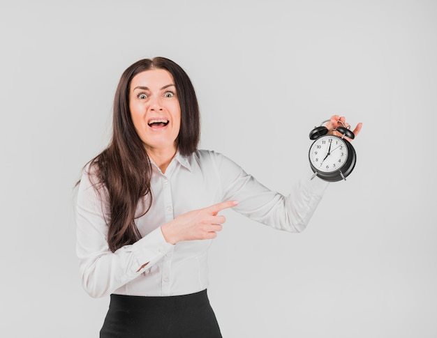 Female with horrified face pointing out alarm clock