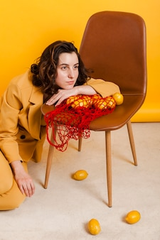 Female with lemons on chair