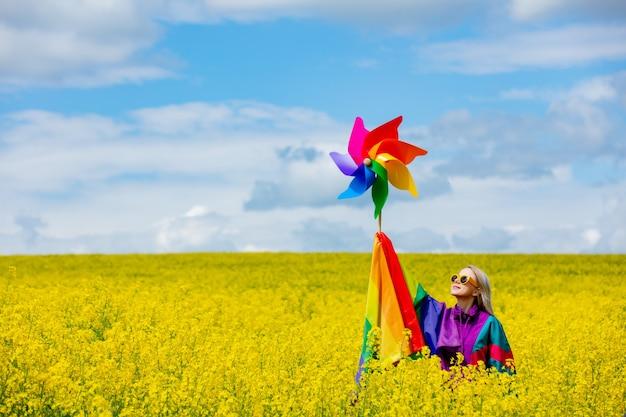 Женщина с радужным флагом лгбт и вертушкой на желтом поле рапса весной