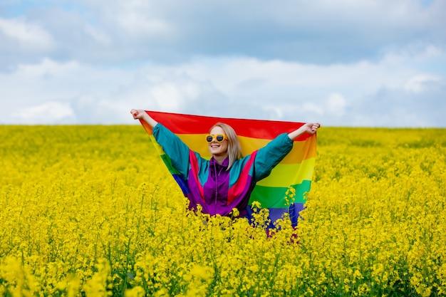 Женщина с радужным флагом лгбт на желтом поле рапса весной