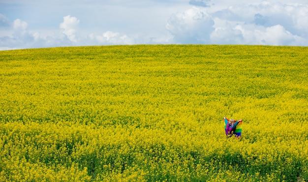 봄에 노란 유채 필드에 lgbt 무지개 깃발을 가진 여성
