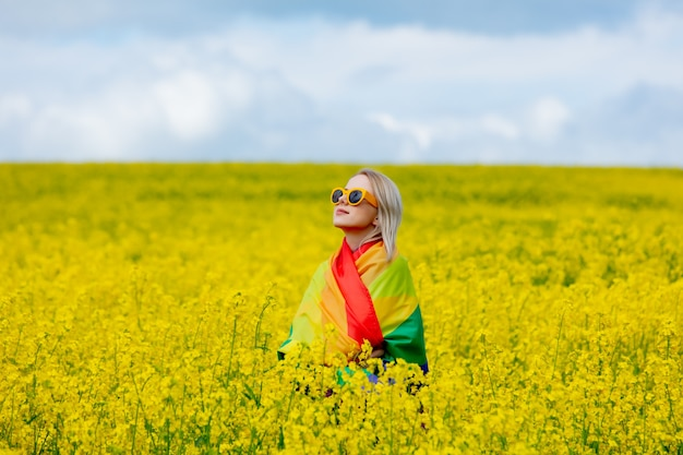 Female with lgbt rainbow flag on yellow rapeseed field in spring