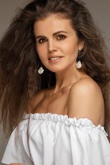 Девушка с распущенными волосами и блузкой, спускающейся ниже плеч, смотрит в камеру.