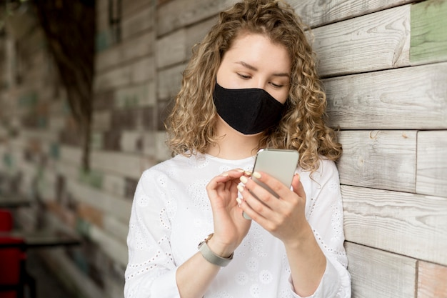 Female with mask using phone