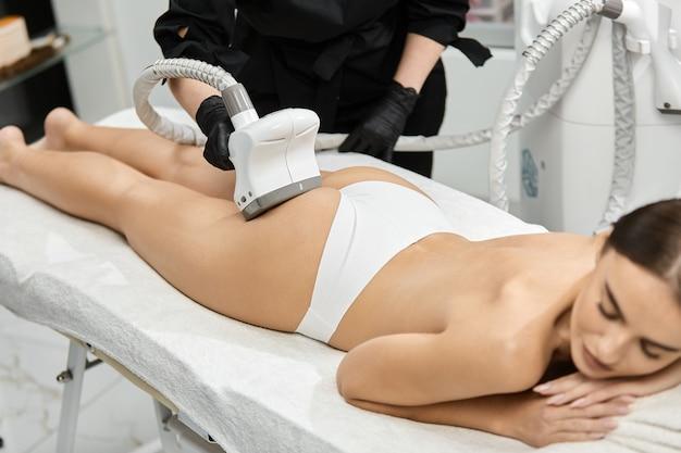 Женщина с идеальным телом, лежащая на спа-кровати и получающая лечение ягодиц профессиональным антицеллюлитным устройством