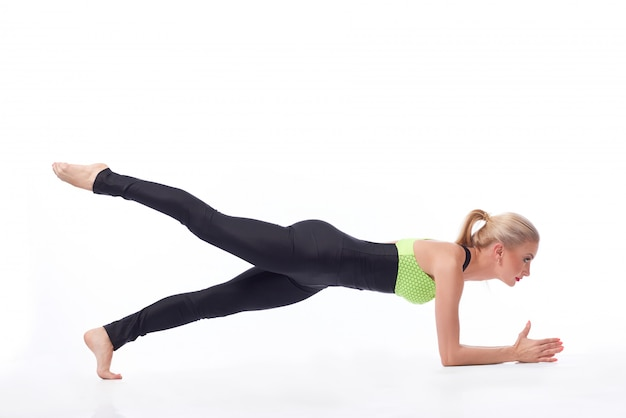 彼女の足を上げる板張りの運動を行う完璧なスポーティな引き締まった体を持つ女性