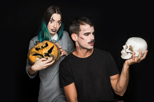 Female with pumpkin and man with skull