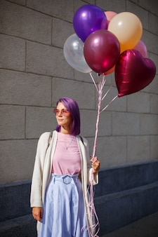 Female with purple hair in glasses with balloons looking to the right side