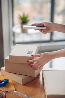 Женщина с красными ногтями держит смартфон над картонной коробкой