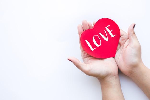 愛のメッセージを示す赤い紙のハートの形を持つ女性
