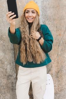 Femmina con skateboard prendendo selfie