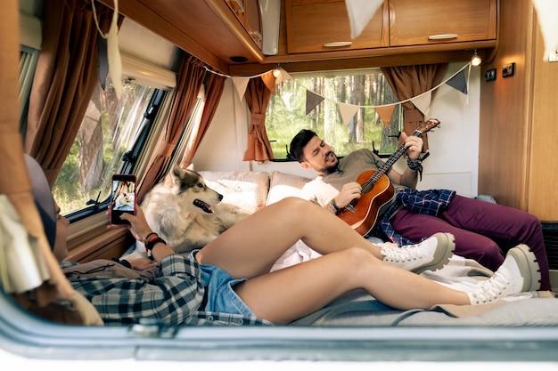 Женщина со смартфоном, снимающая на видео своего парня, играющего на гитаре