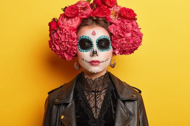 Donna con teschio di zucchero disegnato con un sorriso, indossa una corona di fiori, vestita di abiti neri