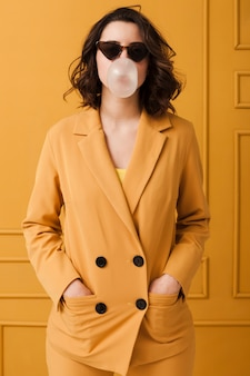 Женщина с очками ест жевательную резинку