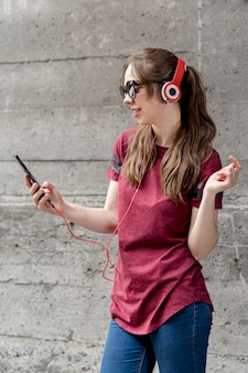Female with sunglasses listening music
