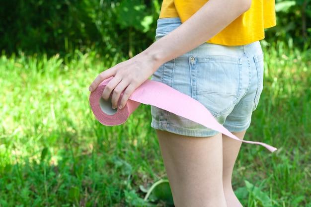 Женщина с туалетной бумагой на открытом воздухе, проблема здравоохранения цистит