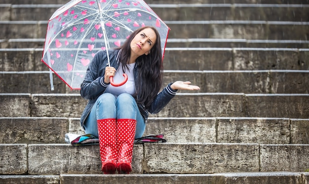 Female with an uncertain face expression sits on the stairs outdoors, holding umbrella in one hand and checking rain drops by the second hand.