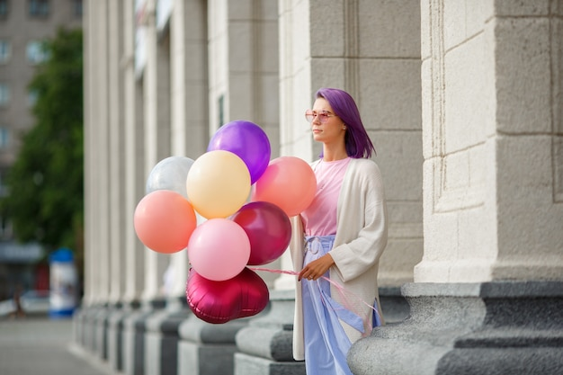 Female with violet hair in pink glasses standing with bunch of baloons