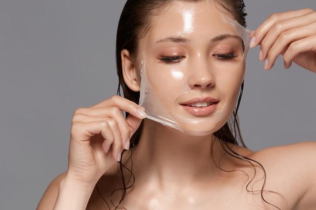 Женщина с мокрыми волосами и обнаженными плечами снимает прозрачную маску-пилинг и смотрит вниз