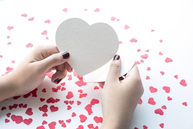 小さな赤いハートの背景に白い紙のハートの形を持つ女性。愛、バレンタイン、結婚式の概念のアイデア
