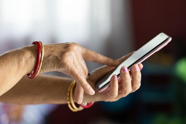 ぼやけた背景のスマートフォンを使用してしわのある手を持つ女性