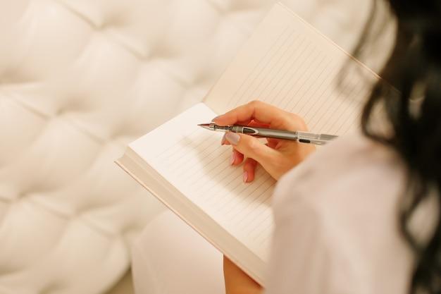 メモ帳を持ってペンで書く女性女性の手。紙に鉛筆、メタルパーカー。