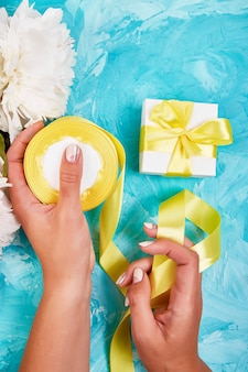 Female woman hand wrapping white gift with yellow ribbon