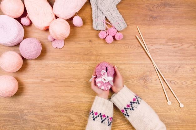 編み針と糸のボールピンクの赤ちゃんのbooteesを持つ女性の女性の手