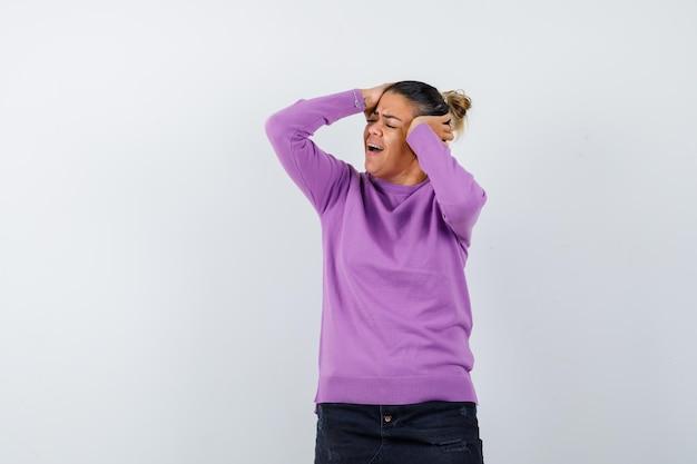 Donna in camicetta di lana che tiene le mani sulla testa e sembra malinconica