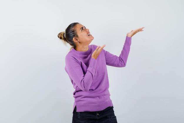 Donna in camicetta di lana che mostra qualcosa sopra e sembra stupita