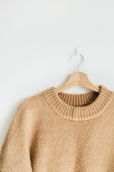 白い壁のハンガーに女性のウールのセーター。