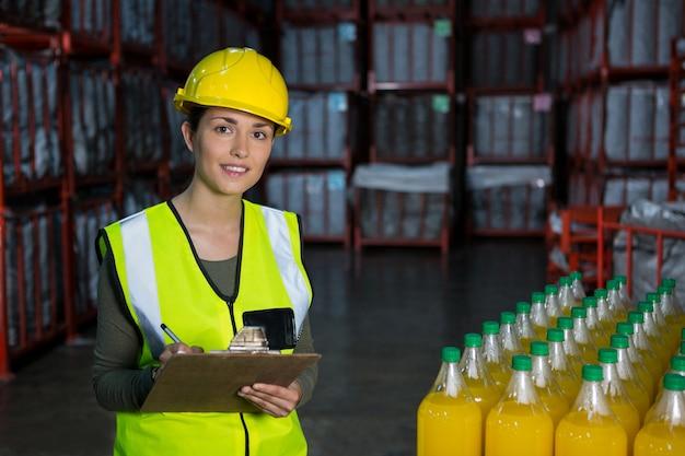Lavoratore di sesso femminile che controlla le bottiglie di succo in fabbrica