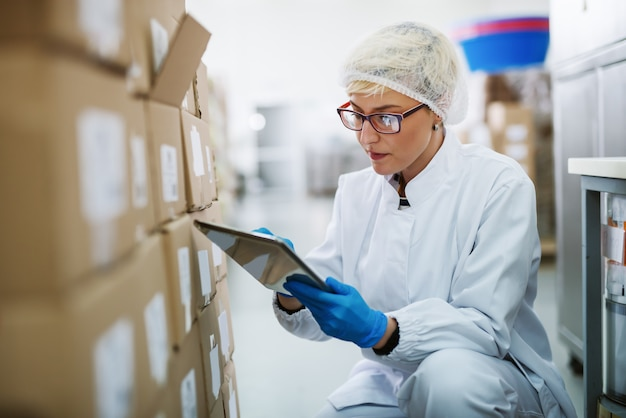 Female worker crouching and using tablet for stock control.