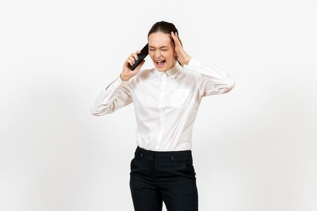Female worker in elegant white blouse talking on phone on light white