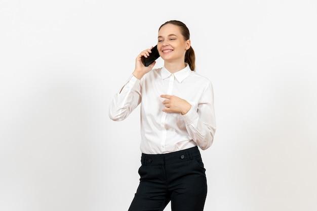 Female worker in elegant white blouse talking on phone on white
